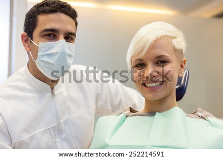 photo of caucasian male dentist sitting next to his smiling female patient and looking towards the camera - stock photo