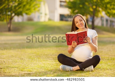 Photo of caucasian pregnant woman reading a book on a green field