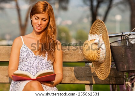 photo of caucasian smiling woman sitting on a bench while reading a book - stock photo