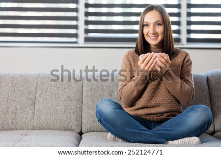 Photo of caucasian smiling woman sitting on the sofa with cup of coffee - stock photo