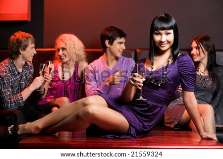Photo of charming female holding flute of champagne with company of friends at background