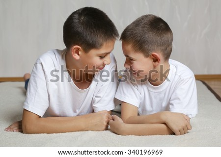 photo of cheerful brothers lying on floor