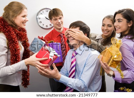 Photo of cheerful businesswoman keeping her hands on man?s eyes while their colleagues preparing gifts for him - stock photo