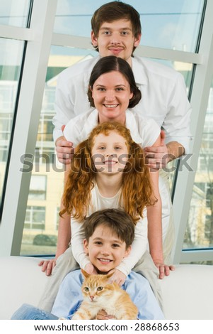 Photo of cheerful children and their parents looking at camera on each other?s heads - stock photo
