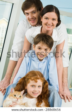 Photo of cheerful children and their parents looking at camera with smiles - stock photo