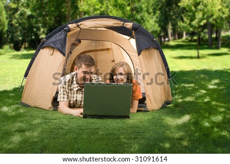 Photo of cheerful girl and guy lying on green grass and looking at laptop monitor in park - stock photo