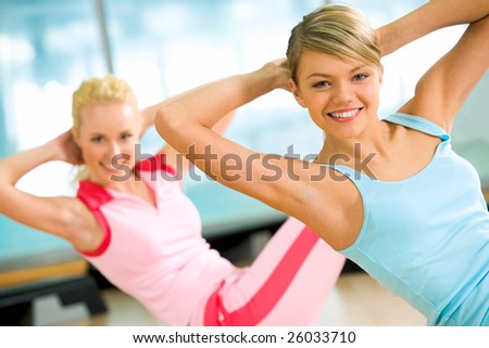 Photo of cheerful girl doing exercise on the floor of sport gym - stock photo