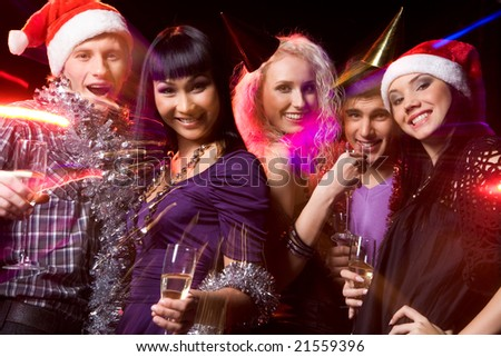 Photo of cheerful people looking at camera with smiles while enjoying Christmas party