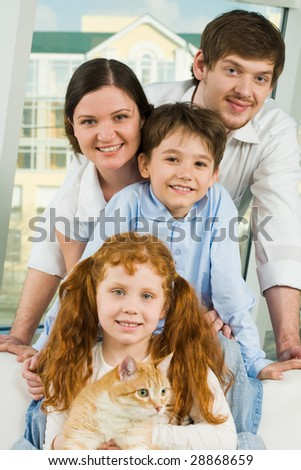 Photo of cheerful siblings with red cat and their parents looking at camera happily - stock photo