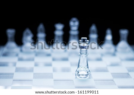 Photo of chess king standing in front of the other colour set in bright background. - stock photo