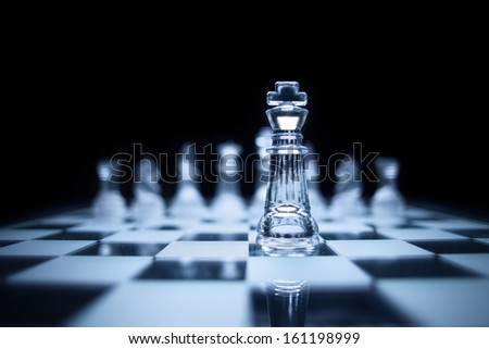 Photo of chess king standing in front of the same colour set in black background. - stock photo
