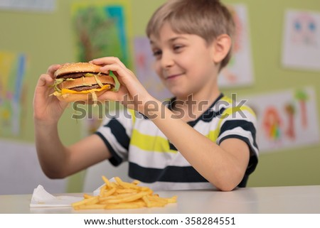 Photo of child with appetite for fat and caloric hamburger  - stock photo