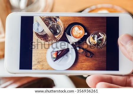 Photo of chocolate cake, cappucino, eyeglass, seasoning and peach tea through smartphone - stock photo