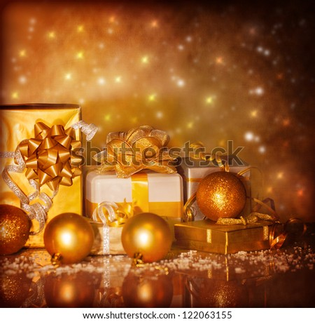 Photo of Christmas present boxes on grunge shiny background, New Year gifts wrapping in beautiful golden paper with ribbon bow, Xmas surprise, luxury festive decorations, Christmastime ornament - stock photo