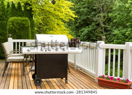 Photo of clean barbecue cooker with cold beer in bucket on cedar deck. Table and colorful trees in background.  - stock photo