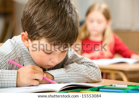 Photo of clever schoolkid writing something in his copybook at lesson on background of classmate - stock photo