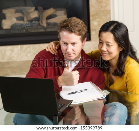 Photo of close mature couple looking at information, man giving thumbs up, on the computer screen together with fireplace in background   - stock photo