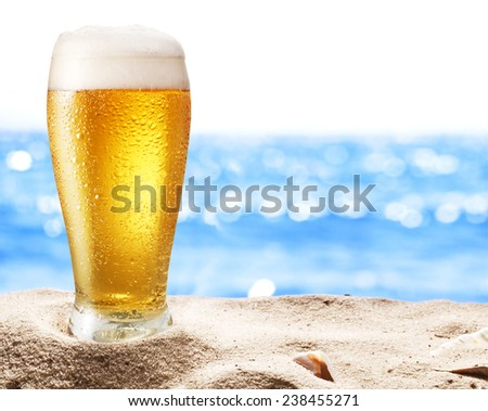 Photo of cold beer botle in the sand. Sparkling sea at the background. - stock photo