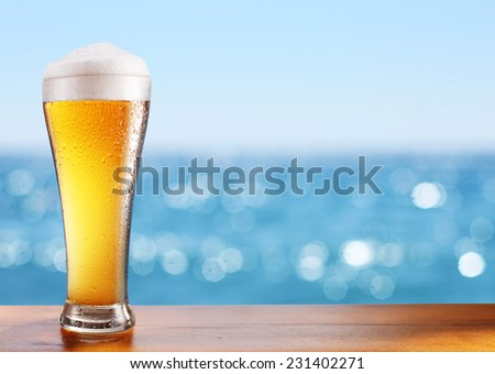 Photo of cold beer glass on the bar table at the open-air cafe. - stock photo
