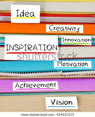 Photo of colorful book stack with bookmarks and labels with INSPIRATION conceptual words - stock photo
