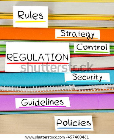 Photo of colorful book stack with bookmarks, labels and REGULATION conceptual words - stock photo