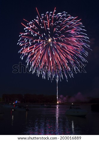 Photo of colorful, exploding fireworks in the night sky during a July 4th holiday celebration in Toledo Ohio Taken  along the Maumee river with boats and colorful reflections in the water. - stock photo