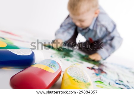 Photo of colorful gouache with painting kid at background - stock photo