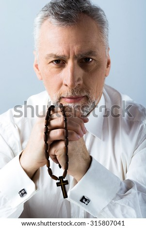 Photo of concentrated old man looking at camera and holding rosary