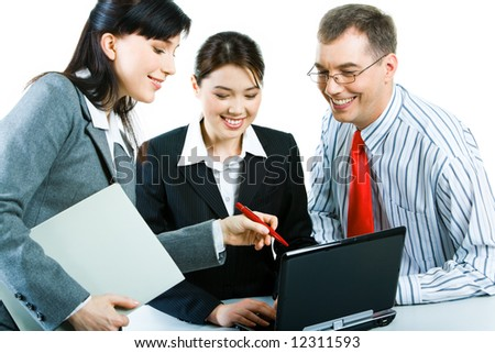 Photo of confident business partners working with laptop at meeting and looking at its screen with smiles