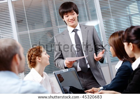 Photo of confident businessman making report to partners at conference - stock photo