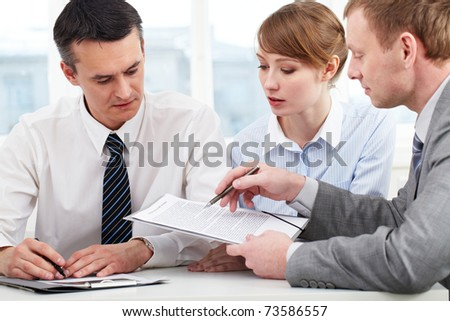 Photo of confident employees discussing papers at meeting - stock photo