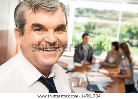Photo of confident older chief smiling in the office - stock photo