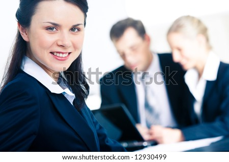 Photo of confident professional looking at camera with smile in working environment