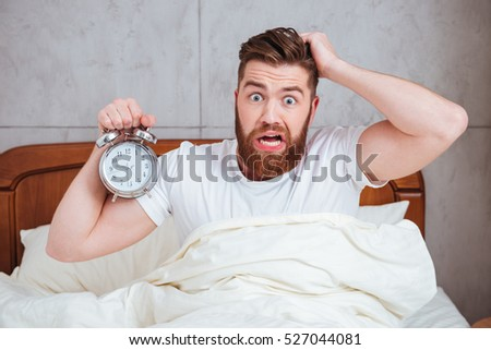 Photo of confused young man sitting in bed while holding alarm clock in hand and showing it to camera. Holding head with hand.