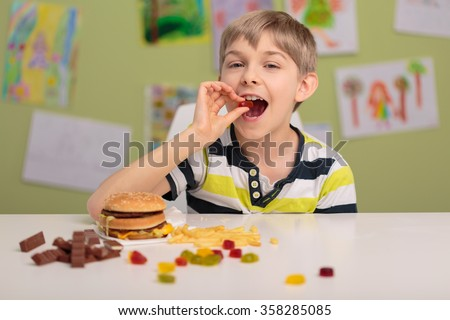 Photo of content child eating sweets and fastfood - stock photo