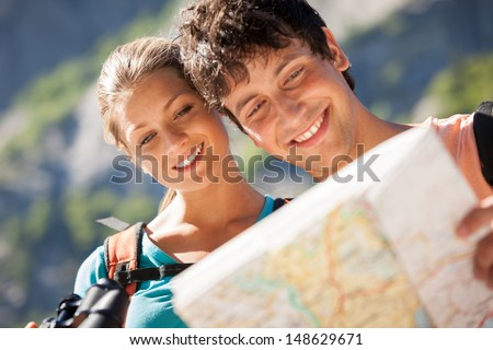 Photo of couple in the mountains looking at the map - stock photo