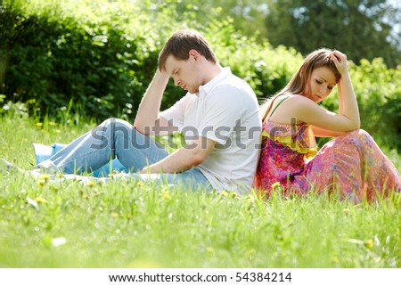 Photo of couple sitting back to back on grass outdoors - stock photo