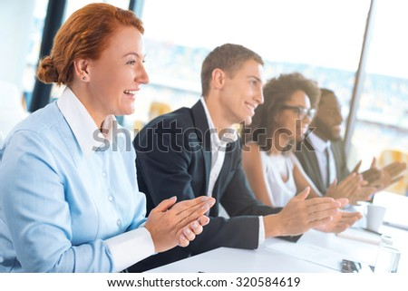 Photo of creative multi ethnic business group. Mixed race business team or commission cheerfully smiling, sitting in row and applauding. White modern office interior with big window - stock photo