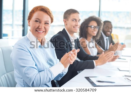 Photo of creative multi ethnic business group. Mixed race business team or commission cheerfully smiling, sitting in row, looking at camera and applauding. White modern office interior with big window - stock photo
