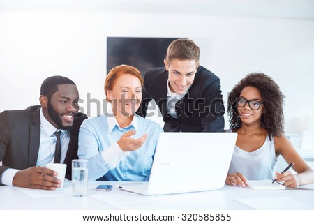Photo of creative multi ethnic business group. Mixed race business team using laptop and discussing project. Everybody smiling. White modern office interior - stock photo