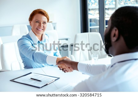 Photo of creative multi ethnic business people. Mixed race business people smiling and shaking hands while meeting. White modern office interior with big window - stock photo