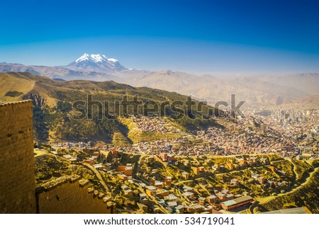 Photo of crowded city and greenery in valley under Huayna Potosi, mountain in Bolivia, South America.