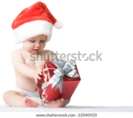 Photo of curious and surprised baby in Santa cap looking at giftbox in his hands - stock photo
