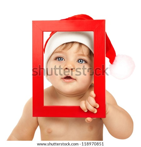 Photo of cute baby boy wearing Santa Claus hat, closeup portrait of curious infant looking through red Christmas frame isolated on white background, happy childhood, winter holidays, New Year eve - stock photo