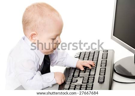 Photo of cute baby typing on keyboard with monitor in front of him - stock photo