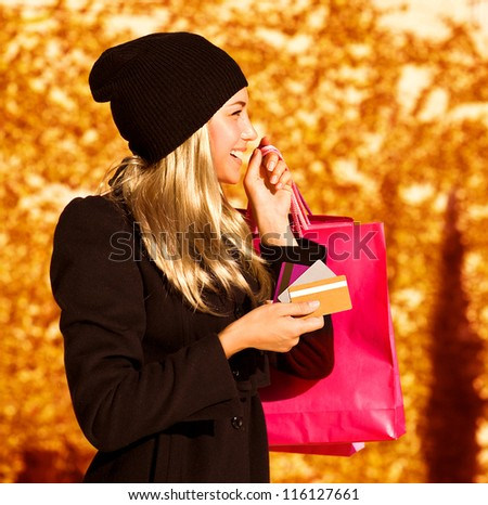 Photo of cute blond girl with pink shopping bag, side view of pretty woman holding paper present bag, beautiful happy shopper over autumn yellow foliage background, seasons sales - stock photo