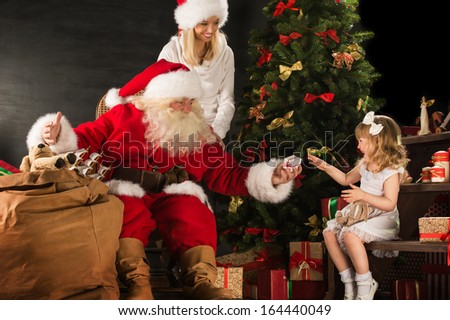 Photo of cute girl and her mother and Santa Claus at home near Christmas tree - stock photo
