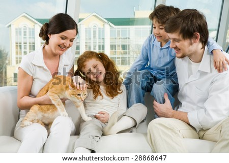 Photo of cute girl caressing pet on her mother?s knees while father and boy looking at it - stock photo