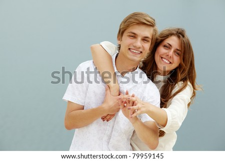 Photo of cute girl embracing handsome male while both laughing - stock photo