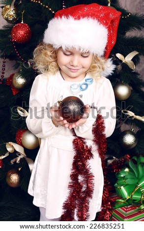 photo of cute little girl with blond curly hair wearing Santa's hat decorating Christmas tree at home - stock photo